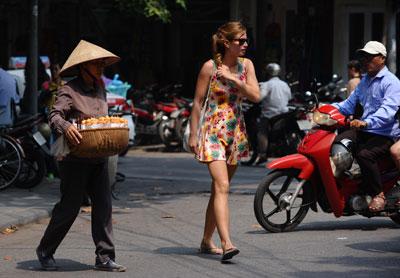 Một người bán hàng rong và một du khách nước ngoài đi qua một đường phố trong khu phố cổ của Hà Nội hôm 9/10/2014. AFP photo