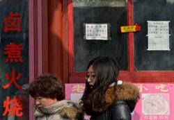 Du khách tại Trung Quốc đi ngang qua nhà hàng hôm 26/2/2013. AFP photo
