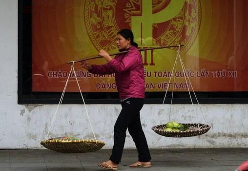 Một phụ nữ gánh hàng rong đi qua một pano tuyên truyền Đại hội đảng toàn quốc trên đường phố Hà Nội ngày 15/01/16.