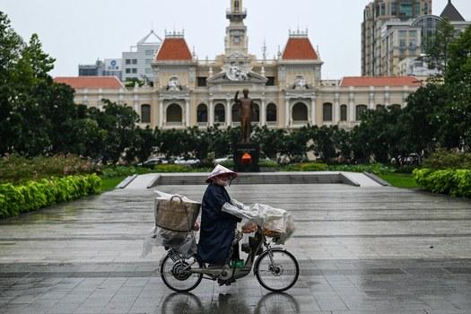 Hình minh hoạ. Một người bán bánh mì đi qua đường phố trung tâm TP Hồ Chí Minh hôm 29/6/2020