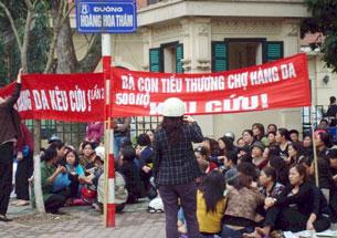 Dân oan chợ Hàng Da căng hai tấm biểu ngữ trước cửa ra vào của quan chức văn phòng Chính Phủ kêu cứu
