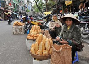 Giá cả tăng làm đôi vai người nghèo càng thêm nặng gánh. AFP