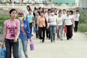 Nữ công nhân đang trên đường đến làm việc ở công xưởng ngoại thành Hà Nội. AFP