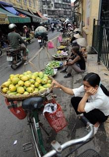 Người buôn gánh bán bưng trong một ngõ hẻm ở Hànội. AFP