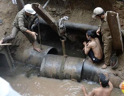 Công nhân sửa chữa đường ống dẫn nước sông Đà bị vỡ. Photo courtesy of vtc.vn