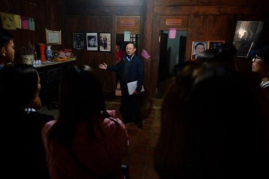 Ông Vương Duy Bảo (người đeo kính, ở giữa bức hình) thuyết minh về lịch sử gia tộc họ Vương cho du khách tham quan Dinh thự Vua Mèo, ở Đồng Văn, Hà Giang. Hình chụp ngày 26/10/18.