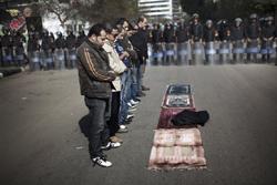 Cảnh sát chống bạo động Ai Cập theo dõi mọi người cầu nguyện bên ngoài nhà thờ Hồi giáo ở Cairo, sau cuộc bạo động lật đổ chính quyền hôm 28/1/2011. AFP Photo.