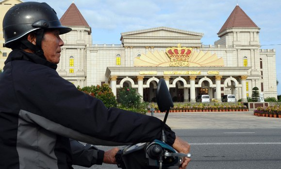Một người chạy xe ôm đang đợi khách trước sòng bạc Crown  ở thành phố biển Đà Nẵng.