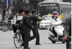 Hai dân phòng phường Ô Chợ Dừa xông ra đường chặn xe. Photo courtesy of wordpress.com