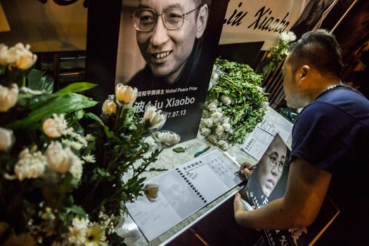 Một người dân bày tỏ thương tiếc trước di ảnh của ông Lưu Hiểu Ba.