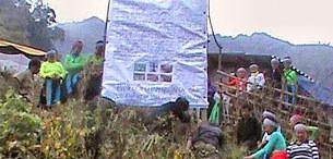 Người H'Mông treo biểu ngữ trước một nhà tang lễ (nhà đòn) nhằm phản đối nhà cầm quyền vu khống đạo Dương Văn Mình