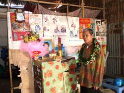 Ảnh chụp anh Trương Văn Sương bên di ảnh vợ ngày được tạm tha về sau hơn 33 năm tù. Tại ngôi nhà nghèo nàn người vợ mỏi mòn đợi chờ đã không còn để đón anh. (tháng 7,2010). RFA file.