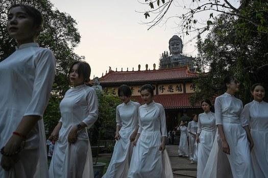Hình minh hoạ. Những phụ nữ Việt Nam đi qua một tượng Phật tại chùa Khai Nguyên ở Sơn Tây, ngoại thành Hà Nội hôm 18/5/2019