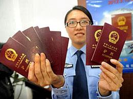 Một nữ công an Trung Quốc ở Giang Tô cầm trên tay những hộ chiếu điện tử mới hôm 08-05-2012. AFP
