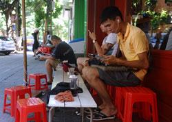 Giới trẻ VN sử dụng iPad tại một quán cà phê vỉa hè Hà Nội hôm 01/8/2013. AFP