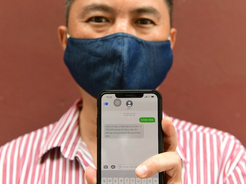 Hình minh hoạ. Người dân với tin nhắn trên điện thoại về đóng góp cho quỹ vaccine