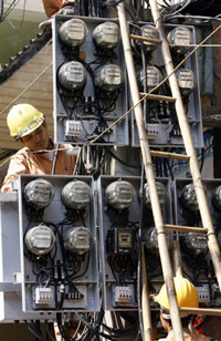 Công nhân ngành điện đang kiểm tra đồng hồ điện tại Hà Nội. AFP PHOTO.
