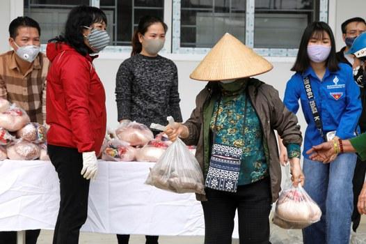 Một phụ nữ nhận thức ăn quyên góp cho người nghèo trong đợt dịch COVID-19 tại Hà Nội, ngày 7 tháng 4 năm 2020.
