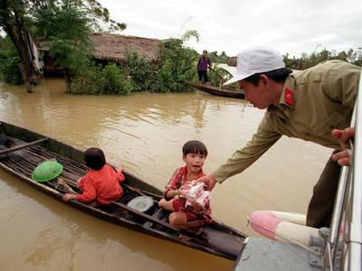 Trẻ em chèo thuyền nhận lương thực cứu trợ mùa lũ ở Quảng Bình.