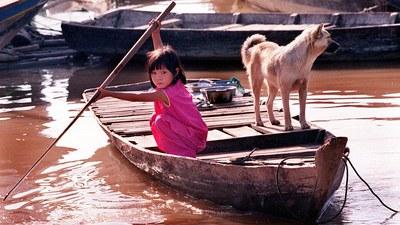 Hình minh hoạ. Một em bé Việt Nam ở Campuchia cùng một con chó trên một chiếc thuyền ở một làng nổi tại dòng Mekong, Phnom Penh.