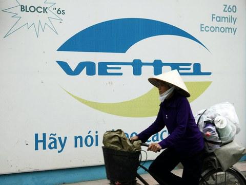 Hình minh hoạ. Một người dân đạp xe qua tấm biển quảng cáo Viettel ở Hà Nội năm 2007