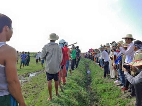 Đoàn ngừơi Việt (bên trái) dàn hàng ngang ngăn cản đoàn kiểm tra biên giới của Campuchia (bên phải) không cho vào phần đất ranh giới của hai nước.
