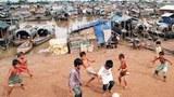 Trẻ em Việt Nam đang chơi đá bóng trên bờ gần những chiếc ghe, xuồng cũng chính là nhà