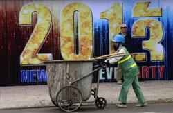 Một công nhân quét rác đẩy xe ngang một pano đón chào năm mới 2013 tại Hà Nội. AFP photo