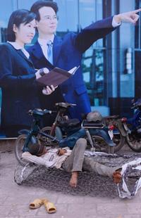 Một người nhập cư nằm nghỉ bên cạnh một poster công bố dự án phát triển ở trung tâm TP HCM hôm 12/4/2011. AFP photo