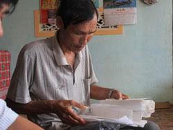 Ông Lê Vinh và xấp giấy tờ nộp phạt cho phía Trung Quốc vào năm 2003 và 2009.