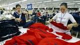 Công nhân xưởng sản xuất quần áo thể thao cho hãng Nike ở Nhà Bè đang xem xét lại phẩm chất hàng hôm 15/02/2003.