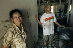 Chị Pham Nhiem và Anh Bui Chien trong căn nhà của họ bị tàn phá bởi cơn bão Katrina ở Mississippi năm 2005. AFP Photo/Stan Honda