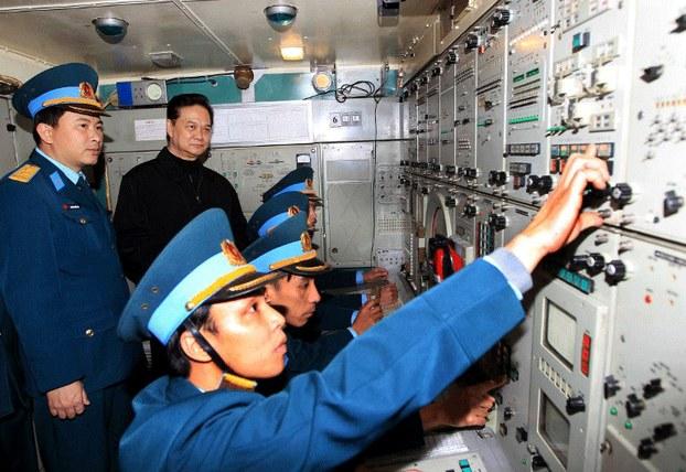 Thủ tướng Nguyễn Tấn Dũng quan sát  các binh sĩ Việt Nam vận hành hệ thống điều khiển tên lửa phòng không S-300 do Nga chế tạo, trong chuyến thăm tiểu đoàn tên lửa phòng không 64 thuộc sư đoàn phòng không 361 đóng tại Hà Nội , hôm 13/01/2014.