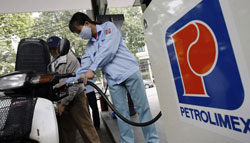 Nhân viên một cây xăng của Petrolimex đang đổ xăng cho khách. AFP photo