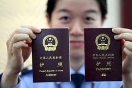 Một nữ công an Trung Quốc ở Giang Tô so sánh hộ chiếu Trung Quốc cũ (bên trái) và hộ chiếu điện tử mới (bên phải) hôm 14-05-2012.AFP