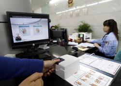 Một người dân Trung Quốc đang lấy dấu vân tay để làm hộ chiếu mẫu mới hôm 15/5/2012. AFP photo
