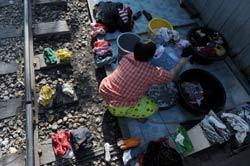 Một phụ nữ sống bên đường rày xe lửa ở thủ đô Bangkok năm 2009. AFP photo