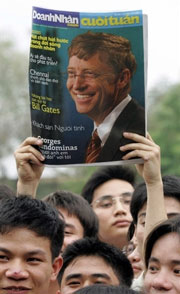 """Sinh viên trường đại học bách khoa Hà Nội nâng cao tờ báo có hình """"Thần Tượng Bill Gates"""" trong dịp ông đến thăm trường hôm 15-6-2006.AFP"""