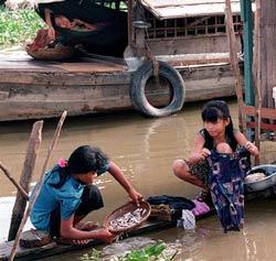 Một bé gái Campuchia (T) và một bé gái VN (P) tại một nmgôi làng ở Phnom Penh. AFP photo