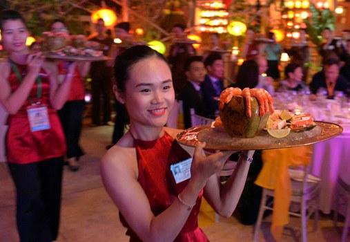 Hình ảnh những nữ lễ tân mặc áo yếm bê khay đồ ăn tiếp khách APEC.