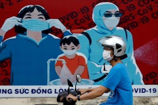 Hình minh hoạ. Người dân đi qua tấm biển kêu gọi phòng chống COVID-19 ở Hà Nội hôm 31/7/2020