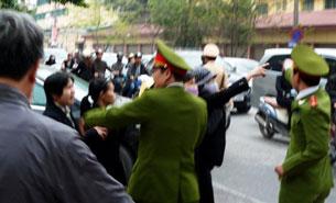 Công An ngăn cản một số người dân bên ngoài tòa án Hà Nội, ngày 04 tháng 04 năm 2011. AFP