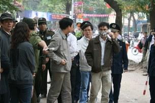 Luật sư Lê Quốc Quân đang đứng ôn hòa bên đường phía ngoài khu vực tòa án khi đang xử TS Cù Huy Hà Vũ, thì bị bắt đi.