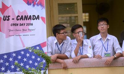 Học sinh một trường trung học ở Hà Nội đứng cạnh một tấm áp phích quảng cáo du học Mỹ - Canada ngày 4 tháng 10 năm 2016.