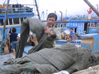 Một ngư dân Việt cuốn lưới trên tàu đánh cá tại cảng Thọ Quang, Đà Nẵng, hôm 26/3/2016.