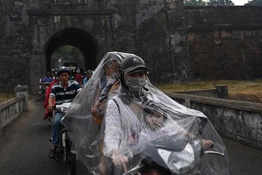 Một phụ nữ chở hai con dưới trời mưa ở Huế. Hình chụp ngày 27/04/19.