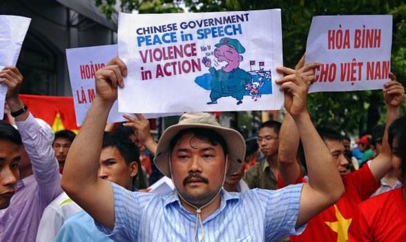 Nhà hoạt động dân chủ Nguyễn Chí Tuyến cùng người biểu tình giương cao những tấm bảng chống Trung Quốc, gần đại sứ quán Trung Quốc tại Hà Nội ngày 19/6/2011.