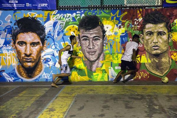 Trẻ em Brazil chơi bóng trước một bức tranh trên tường với cầu thủ bóng đá người Argentina Lionel Messi (T), cầu thủ của Brazil Neymar da Silva Santos Junior (giữa) và cầu thủ Bồ Đào Nha Christiano Ronaldo hôm 08/6/2014.