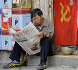 Một công nhân lao động đang đọc báo trong giờ nghỉ. AFP