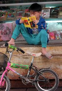 Trẻ em đọc sách bên ngoài một tiệm bán sách ở ngọai ô Hà Nội. AFP photo